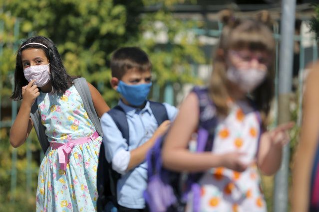 Alegra Bajrami, left, wearing a face mask to protect against coronavirus, enters the school yard on the first day of classes in the new academic year during the ongoing coronavirus pandemic, in the capital Pristina, Kosovo, Monday, September 14, 2020. (Photo by Visar Kryeziu/AP Photo)