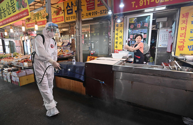 A health official wearing protective gear sprays disinfectant at a market near the Sarang Jeil Church, a new coronavirus infection cluster, in Seoul on August 18, 2020. South Korea on August 18 ordered nightclubs, museums and buffet restaurants closed and banned large-scale gatherings in and around the capital as a burst of new coronavirus cases sparked fears of a major second wave. (Photo by Jung Yeon-je/AFP Photo)