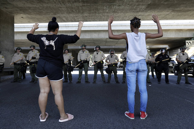 "Two women raise their hands in front of a line of police during a protest Wednesday, September 28, 2016, in El Cajon, Calif. Dozens of demonstrators on Wednesday protested the killing of a black man shot by an officer after authorities said the man pulled an object from a pocket, pointed it and assumed a ""shooting stance"". (Photo by Gregory Bull/AP Photo)"