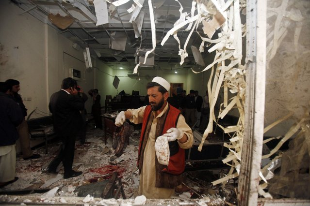 A security official collects evidences at the site of bomb blast in a judicial compound in Peshawar March 18, 2013. Two suicide bombers attacked a judicial compound in the Pakistani city of Peshawar on Monday, killing four people and taking hostages, officials said. (Photo by Fayaz Aziz/Reuters)