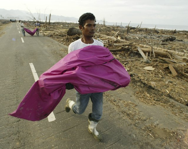 Residents in the tsunami-ravaged Indonesian town of Leupung in Aceh carry bodies to a freshly dug grave in this January 27, 2005 file photo. (Photo by Enny Nuraheni/Reuters)