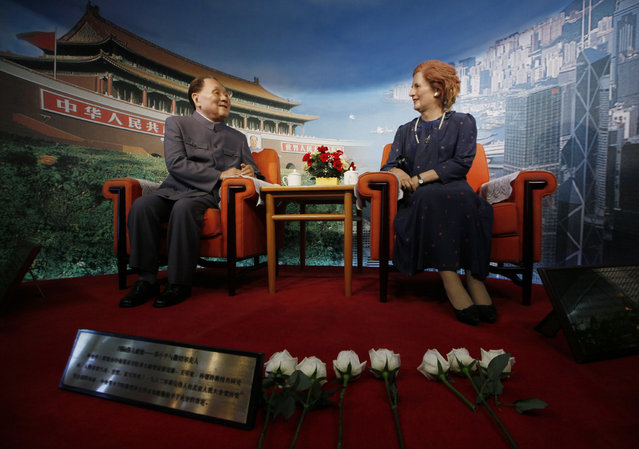 """Flowers are laid by staff members in front of the wax statue of former British Prime Minister Margaret Thatcher, right, following her death in an exhibition center in Shenzhen, China Tuesday, April 9, 2013. Margaret Thatcher, the combative """"Iron Lady"""" who infuriated European allies, found a fellow believer in Ronald Reagan and transformed her country by a ruthless dedication to free markets in 11 bruising years as prime minister, died Monday, April 8, 2013. She was 87 years old. The wax statue at left is of former Chinese leader Deng Xiaoping. (Photo by in Cheung/AP Photo)"""