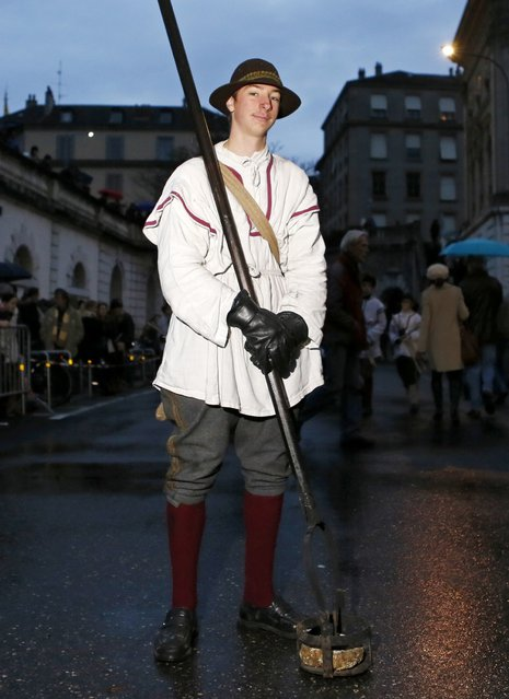A member of Compagnie 1602 playing the role of a torch carrier poses before a procession in Geneva December 14, 2014. (Photo by Pierre Albouy/Reuters)