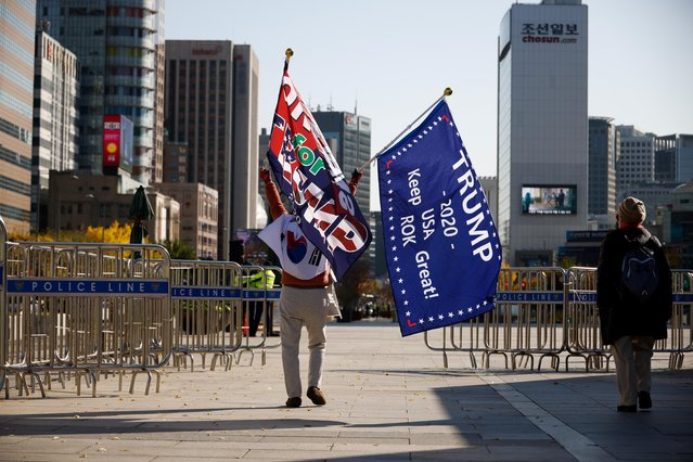 A member of a conservative group waves a flag bearing a message of support for Donald Trump in the 2020 U.S. presidential election in front of the U.S. embassy in Seoul, South Korea, November 4, 2020. (Photo by Kim Hong-Ji/Reuters)