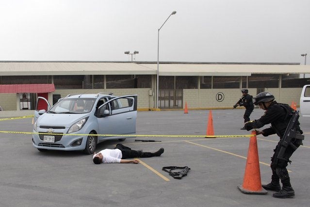 Members of the Fuerza Civil (Civil Force) police unit cordon off a simulated crime scene during a media presentation to show the police model that the federal government wants for the rest of the country, at the police academy in Monterrey December 17, 2014. (Photo by Daniel Becerril/Reuters)