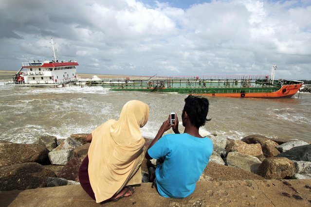 Locals take pictures of an Indonesian tanker that ran aground near Narathiwat in southern Thailand December 19, 2014. (Photo by Surapan Boonthanom/Reuters)