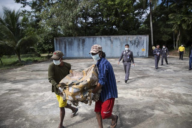 Personal possessions of 2004 tsunami victims are carried from a container to be photographed outside a police station in Takua Pa, in Phang Nga province December 19, 2014. (Photo by Damir Sagolj/Reuters)