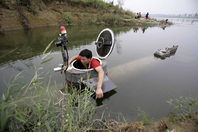 Tao Xiangli gets out of his homemade submarine after operating it in a lake on the outskirts of Beijing September 3, 2009. Amateur inventor Tao, 34,  made a fully functional submarine, which has a periscope, depth control tanks, electric motors, manometer, and two propellers, from old oil barrels and tools which he bought at a second-hand market. He took 2 years to invent and test the submarine which costs 30,000 yuan ($4,385). (Photo by Christina Hu/Reuters)