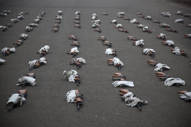 Guns and gloves of India's Air Force soldiers lie on a road during rehearsals for the upcoming Republic Day parade in New Delhi, India, Tuesday, December 23, 2014. India marks Republic Day on January 26 with military parades across the country. (Photo by Tsering Topgyal/AP Photo)