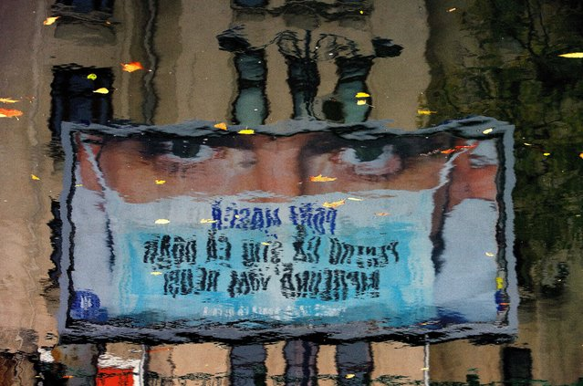 "A government awareness poster for wearing surgical masks is seen reflected and upside-down in the Dambovita river in Bucharest, Romania, 19 November 2020. The poster, depicting a man wearing a surgical mask, reads: ""I WEAR A MASK BECAUSE I KNOW THAT ONLY TOGETHER WE WILL SUCCEED!"". As the number of COVID-19 infections increased, authorities decided that wearing a protective mask should become mandatory at all times in all public places. (Photo by Robert Ghement/EPA/EFE)"