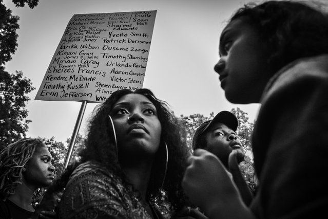 Erika Totten, L, of Alexandria, VA, holds a sign listing some of the names of people killed by police in the United States as hundreds of people gather at Meridian Hill (Malcolm X) Park for a peaceful vigil and moment of silence in honor of innocent lives lost and those who have been affected by police brutality on Thursday, August 14, 2014, in Washington, DC. (Photo by Jahi Chikwendiu/The Washington Post)