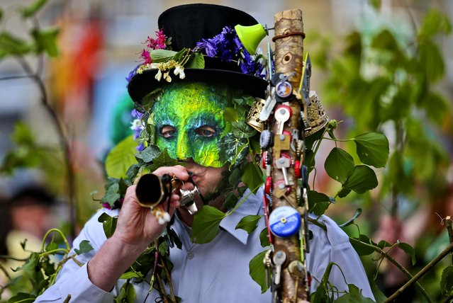 A performer with the Hal-an-Tow pageant blows his horn as part of the Helston Flora Day celebrations  in Cornwall, England, on May 8, 2013. The annual event is one of the UK's oldest customs, celebrating the passing of Winter and the arrival of Spring. (Photo by Matt Cardy/Getty Images)