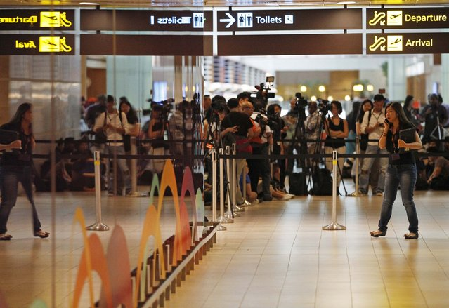 Journalists crowd the waiting area for next-of-kin and relatives of passengers onboard AirAsia flight QZ8501 at Changi Airport in Singapore December 28, 2014. (Photo by Edgar Su/Reuters)