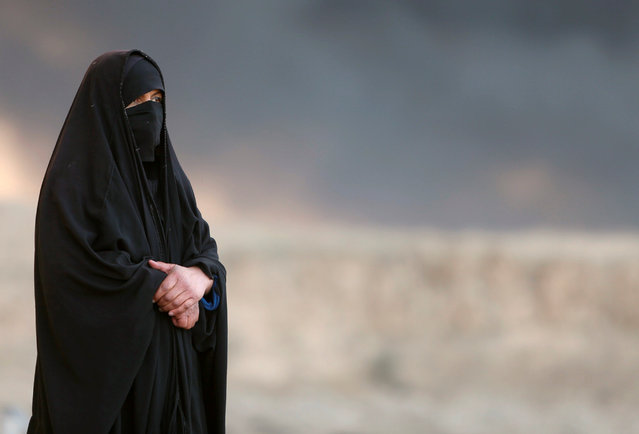 A woman returns to her village after it was liberated from Islamic State militants, south of Mosul in Qayyara, Iraq, October 22, 2016. The fumes in the background are from oil wells that were set ablaze by Islamic State militants. (Photo by Alaa Al-Marjani/Reuters)