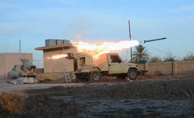 A vehicle belonging to Shi'ite fighters fires a multiple rocket launcher during clashes with the Islamic State on at the outskirt of Balad, north of Baghdad December 26, 2014. (Photo by Reuters/Stringer)