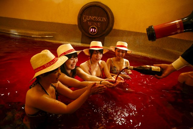 A man pours wine into the hands of a women as they sit in a hot bath with coloured water representing wine at the Hakone Kowaki-en Yunessun spa resort during an event marking Beaujolais Nouveau Day in Hakone west of Tokyo, November 19, 2015. (Photo by Thomas Peter/Reuters)
