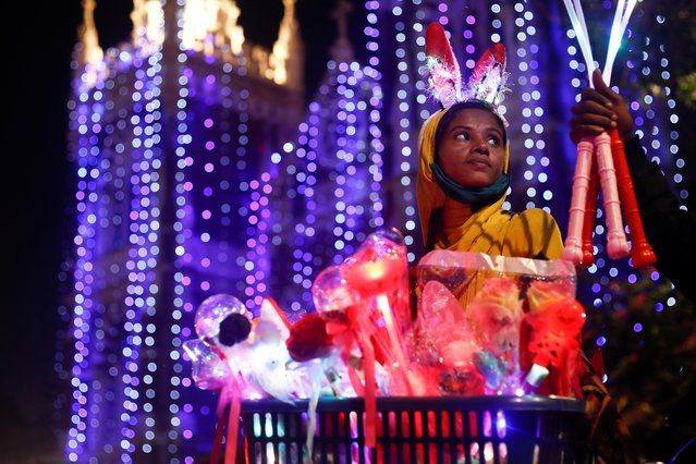 A woman sells props outside a church on as members of India's Christian community celebrate Christmas eve in Mumbai, India, December 24, 2020. (Photo by Francis Mascarenhas/Reuters)