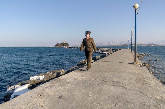 A female soldier walks down a jetty in Wonsan, Feburary 2012. (Eric Testroete)