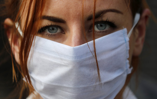 An member of the group 'Pause the System' wears a face mask as she protests in front of the entrance to Downing Street in London, Friday, March 20, 2020. For most people, the new coronavirus causes only mild or moderate symptoms, such as fever and cough. For some, especially older adults and people with existing health problems, it can cause more severe illness, including pneumonia. (Photo by Frank Augstein/AP Photo)