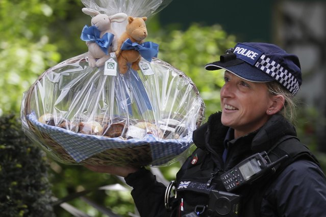 A police officer carries a gift basket for Prime Minister Boris Johnson and his partner Carrie Symonds sent on occasion of the birth of their son into No. 10 Downing Street in London, Britain, 01 May 2020. The United Kingdom's 66 million inhabitants are living through their sixth consecutive week of nationwide lockdown prompted by the ongoing pandemic of the COVID-19 disease caused by the SARS-CoV-2 coronavirus. (Photo by Kirsty Wigglesworth/AP Photo)
