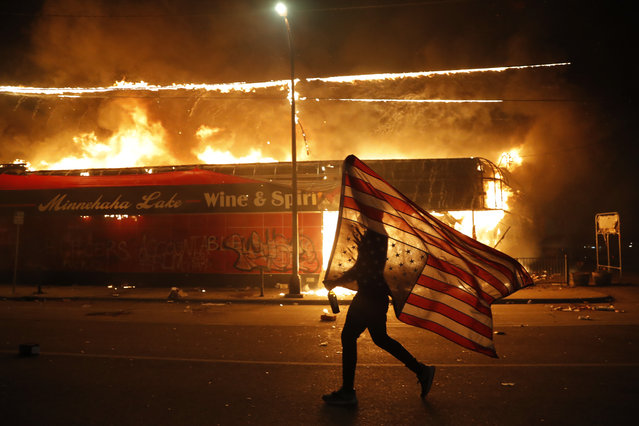 A protester carries a U.S. flag upside down, a sign of distress, next to a burning building Thursday, May 28, 2020, in Minneapolis. Protests over the death of George Floyd, a black man who died in police custody Monday, broke out in Minneapolis for a third straight night. (Photo by Julio Cortez/AP Photo)