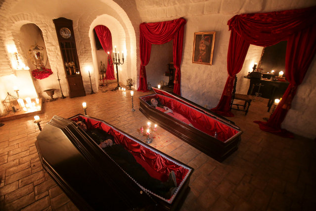 Tami and Robin Varma lie in red velvet-trimmed coffins while posing for media representatives in one of the rooms of Bran Castle, in Brasov county, Romania, October 31, 2016. (Photo by Octav Ganea/Reuters/Inquam Photos)