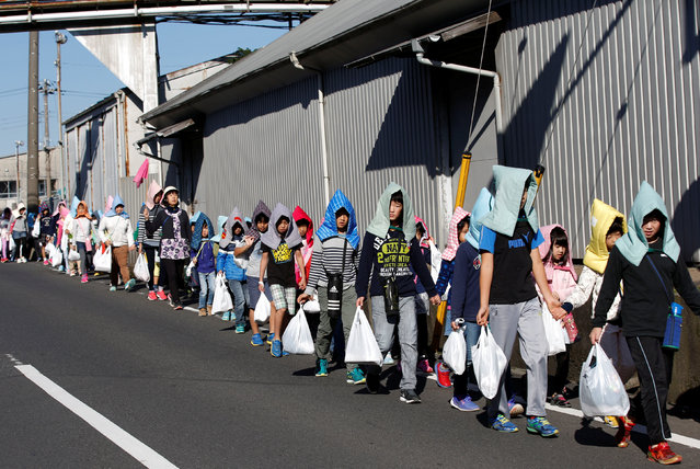 School children wearing padded hoods to protect them from falling debris make their way to an evacuation shelter on a hill during a tsunami simulation drill ahead of World Tsunami Awareness Day at Futaba elementary school in Choshi, Chiba Prefecture, Japan, November 4, 2016. (Photo by Kim Kyung-Hoon/Reuters)
