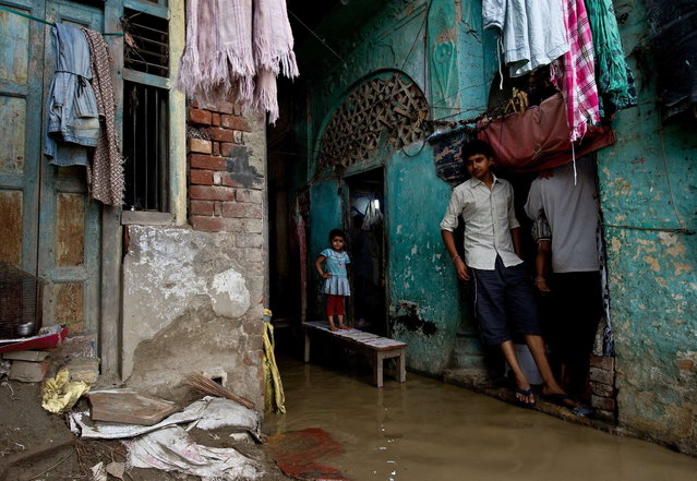 An Indian girl stands on a bench as rising waters of the Yamuna river flowed into her home on the ghats in New Delhi on June 18, 2013. Monsoon rains have arrived early in northern India, leaving at least 64 people dead and thousands stranded, officials said June 18. (Photo by Manan Vatsyayana/AFP Photo)