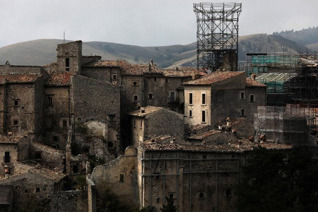 Metal frames support what is left of a medieval tower, as works are in progress to reconstruct it after it collapsed in the 2009 earthquake, in Santo Stefano di Sessanio in in the province of L'Aquila in Abruzzo, inside the national park of the Gran Sasso e Monti della Laga, Italy, September 22, 2016. (Photo by Siegfried Modola/Reuters)