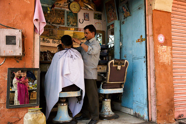 """""""At the barber shop"""". A woman holding her baby is waiting the husband at the barber shop. Location: Jaipur, Rajasthan, India. (Photo and caption by Massimiliano De Santis/National Geographic Traveler Photo Contest)"""