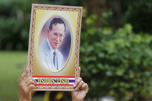 "A supporter of Thailand's King Bhumibol Adulyadej holds a portraait of him outside Siriraj hospital, where a group gathered to mark his 88th birthday, in Bangkok December 5, 2015.  Words on portrait read, ""Long live the king!"". (Photo by Jorge Silva/Reuters)"
