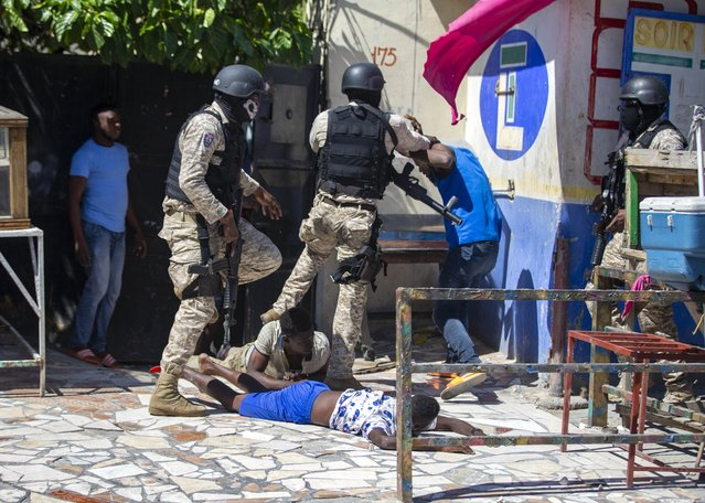 Police officers detain demonstrators during a protest to demand the resignation of Haitian President Jovenel Moise in Port-au-Prince, Haiti, Sunday, February 7, 2021. (Photo by Dieu Nalio Chery/AP Photo)