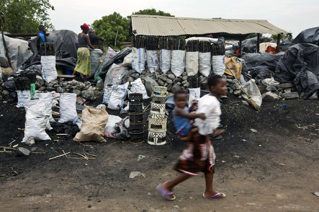 Children walk past charcoal sellers in Kitwe, Zambia January 17, 2015. (Photo by Rogan Ward/Reuters)