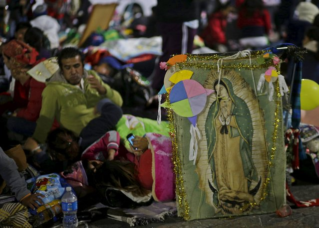 Pilgrims rest beside an image of the Virgin of Guadalupe next to an improvised camp site at the Basilica of Guadalupe during the annual pilgrimage in honor of the Virgin of Guadalupe, patron saint of Mexican Catholics, in Mexico City, Mexico December 12, 2015. (Photo by Henry Romero/Reuters)