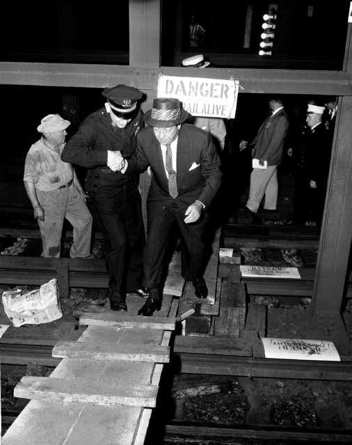 Mayor Robert Wagner of New York moves across damaged tracks in the Astor Place Station of the IRT's Lexington Avenue line with assistance of inspector Edward Stanley, left, during a brief tour of the station, July 1, 1956. (Photo by John Lent/AP Photo)