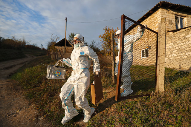 Election officials wearing biohazard suits, for protection against the COVID-19 infection, carry a mobile ballot box while visiting voters with mobility issues during the presidential elections in Hrusova, Moldova, Sunday, November 15, 2020. Moldovans returned to the polls Sunday for the second round of voting in the country's presidential election, facing a choice between the staunchly pro-Russian incumbent and his popular pro-Western challenger after former prime minister, Maia Sandu, who beat the odds to win the first round on November 1 with over 36 percent of to vote, leaving the incumbent, President Igor Dodon, trailing her by over 3.5 points. (Photo by Roveliu Buga/AP Photo)