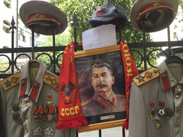 Replicas of Joseph Stalin uniforms are offered to tourists who can rent them and wear them for a picture outside Stalin's bunker in Samara, Russia, on Tuesday, June 26, 2018. Stalin's secret WWII bunker has become the unlikely meeting point for thousands of cheerful fans who have arrived to the city during the World Cup days. (Photo by Luis Andres Henao/AP Photo)