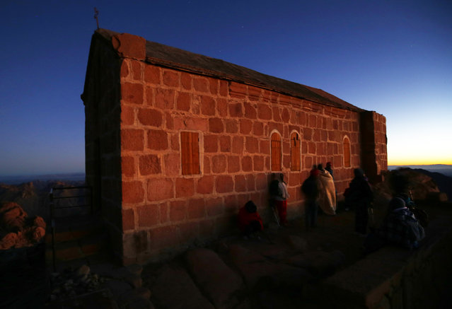 Tourists watch the sunrise and pray outside a church on the summit of Mount Moses, near the city of Saint Catherine, in the Sinai Peninsula, south of Egypt, December 9, 2015. (Photo by Amr Abdallah Dalsh/Reuters)