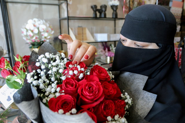 A Saudi woman shops at a florist on Valentine's Day in Riyadh, Saudi Arabia on February 14, 2021. (Photo by Ahmed Yosri/Reuters)