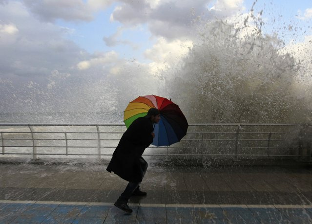 A man plays in front of a wave crashing into Beirut's Corniche, a seaside promenade, as high winds sweep through Lebanon ahead of an impending storm January 6, 2015. (Photo by Jamal Saidi/Reuters)