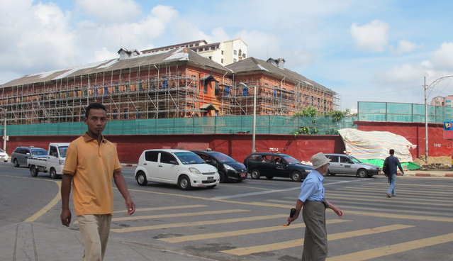 "In this Monday, October 3, 2016 photo, people walk by the Myanmar Railways headquarters under restoration works in Yangon, Myanmar. The Yangon Heritage Trust says Myanmar's largest city and commercial capital is facing its ""last best chance"" to salvage and restore many crumbling colonial treasures. They recently proposed a ""heritage strategy"" for the city that outlines a vision of how to make the city more livable, modern and still affordable as property developers crowd in, while preserving its unique landmarks and neglected green spaces. (Photo by Elaine Kurtenbach/AP Photo)"