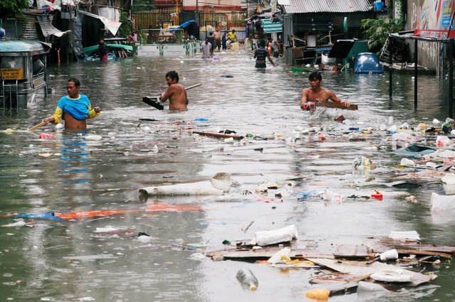 Residents gather plastics and other recyclable materials along a flooded street caused by monsoon rains and Tropical Storm Son-Tinh in Quezon city, Metro Manila, Philippines on July 17, 2018. (Photo by Erik De Castro/Reuters)