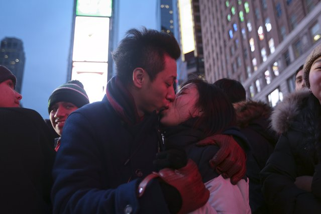 A couple kiss on the ground in a penned off area of Times Square before New Year's Eve celebrations begin in the Manhattan borough of New York, December 31, 2015. (Photo by Carlo Allegri/Reuters)