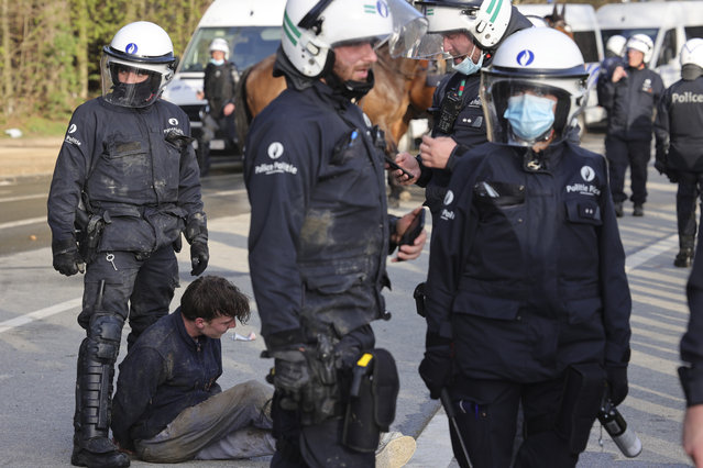 Police detain a man during protests at a park in Brussels, Thursday, April 1, 2021. Belgian police have clashed with a large crowd in one of Brussels largest parks, as thousands of revelers had gathered for an unauthorized event despite coronavirus restrictions. (Photo by Olivier Matthys/AP Photo)