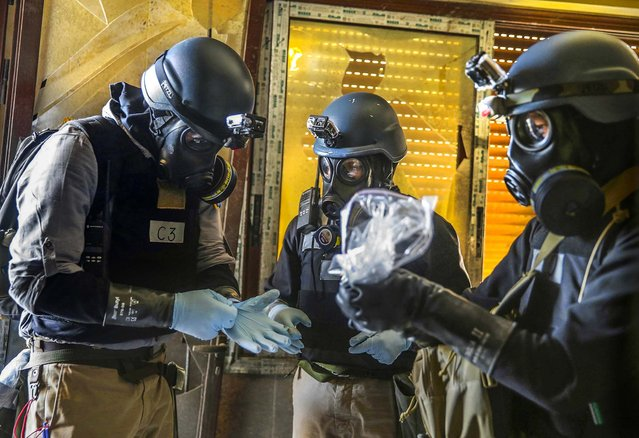 U.N. chemical weapons experts gather items at a site of alleged chemical weapons attack in the Ain Tarma neighborhood of Damascus, on August 29, 2013. (Photo by Mohamed Abdullah/Reuters)