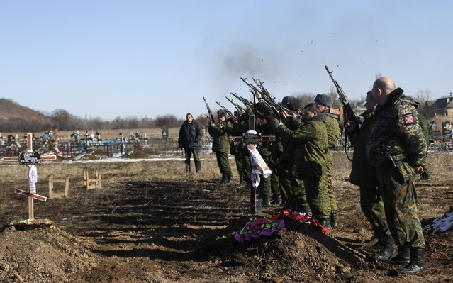 Russia-backed separatist fighters shoot in the air to pay respects to their comrade during a funeral at a cemetery in the east Ukrainian village of Mospino, near the city of Donetsk, Ukraine, on Thursday, February 12, 2015. (Photo by Petr David Josek/AP Photo)