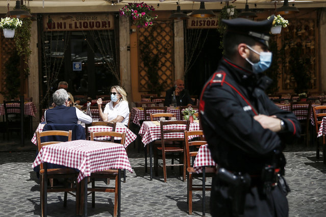 A Carabinieri (Italian paramilitary police) officer patrols as people sit at a restaurant in Rome, Monday, April 26, 2021. Italy's gradual reopening after six months of rotating virus closures is satisfying no one: Too cautious for some, too hasty for others.  Allowing outdoor dining starting Monday is coming too little, too late for restaurant owners whose survival has been threatened by more than a year of on-again, off-again virus closures. (Photo by Cecilia Fabiano/LaPresse via AP Photo)