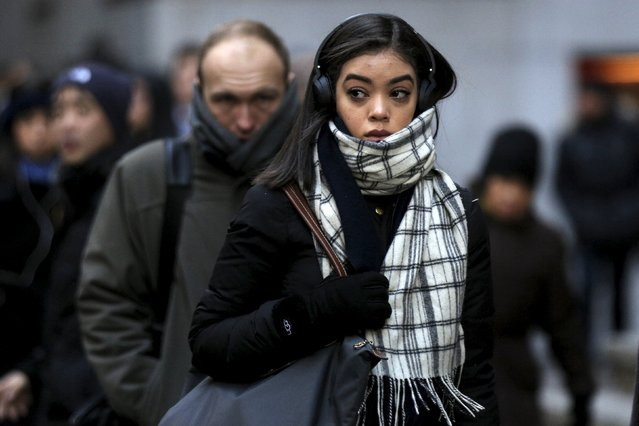 Morning commuters bundle up from the cold during the morning rush on Wall St. in New York, January 5, 2016. (Photo by Brendan McDermid/Reuters)