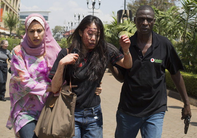 An injured woman (C) is helped out of the Westgate Shopping Centre where gunmens went on a shooting spree, in Nairobi September 21, 2013. (Photo by Siegfried Modola/Reuters)