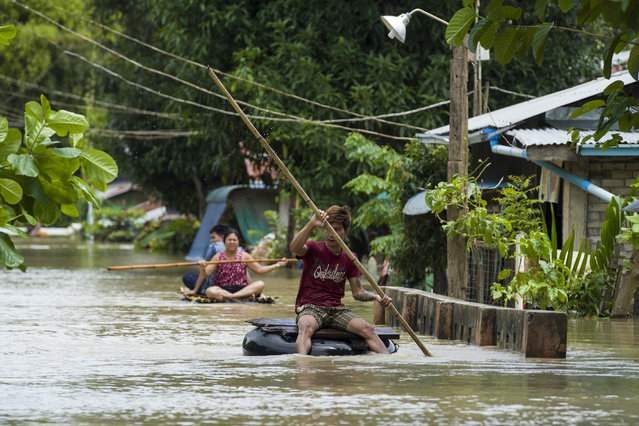 Residents make their way through a flooded road in Taungnu township of Bago region in Myanmar on August 31, 2018. (Photo by Ye Aung Thu/AFP Photo)